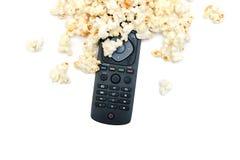 玉米花和电视遥控在白色背景 免版税库存图片