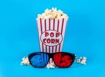 玉米花和3D玻璃在蓝色背景 免版税库存图片