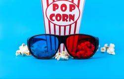 玉米花和3D玻璃在蓝色背景 免版税图库摄影