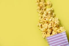 玉米花在黄色顶视图-甜黄油玉米花背景的杯子箱子 免版税库存照片