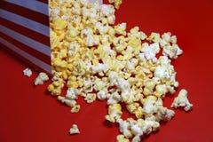 玉米花堆从红色和白皮书箱子的在红色地板上 库存图片