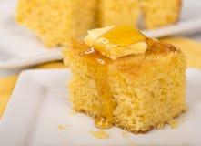 玉米面包用蜂蜜和黄油 免版税库存照片