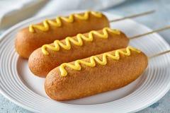 玉米面热狗传统美国corndog街道速食油炸了热狗肉香肠快餐用在上面的芥末 库存照片
