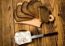 玉米面面包切开了成片断和黄油在木背景 库存照片