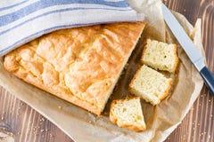 玉米面面包在木背景的和平切开了 库存图片