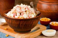 从玉米,鸡蛋,在黏土碗的螃蟹棍子的快餐沙拉在woode 图库摄影