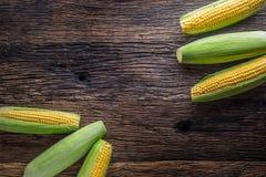 玉米 在老土气橡木桌上的新鲜的玉米 库存照片