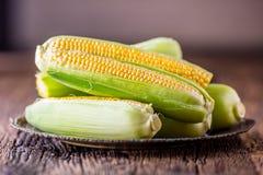 玉米 在老土气橡木桌上的新鲜的玉米 图库摄影