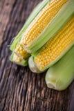 玉米 在老土气橡木桌上的新鲜的玉米 库存图片