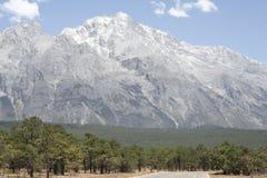 玉龙与树和路的山风景在前景 库存图片