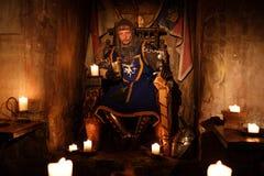 王位的中世纪国王在古老城堡内部 免版税库存图片