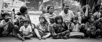 王舍城,印度- 2016年12月4日:一个小组印地安人,妇女和孩子为金钱或食物坐并且乞求游人 库存图片