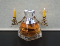 王薇薇,夫人的芬芳,在钢琴大烛台前面的大香水瓶有光亮的蜡烛的 免版税图库摄影