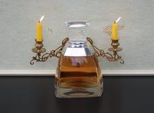 王薇薇,夫人的芬芳,在钢琴大烛台前面的大香水瓶有光亮的蜡烛的 免版税库存照片