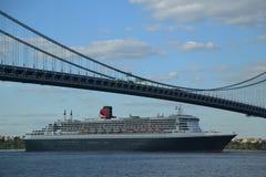 玛丽皇后2游轮在Verrazano桥梁标题下的纽约港口从纽约的横跨大西洋的向南安普敦 免版税库存照片
