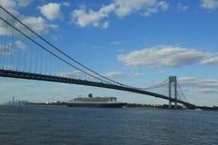 玛丽皇后2游轮在Verrazano桥梁标题下的纽约港口从纽约的横跨大西洋的向南安普敦 免版税库存图片