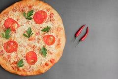 玛格丽塔比萨用蕃茄和两红色辣椒在灰色桌、顶视图和地方上文本的 库存照片