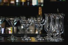 玛格丽塔酒、马蒂尼鸡尾酒、酒和利口酒的玻璃在餐馆的一个酒吧 库存图片