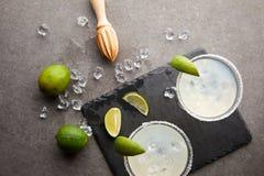 玛格丽塔酒鸡尾酒顶视图与石灰、冰块和木剥削者片断的在灰色桌面 免版税库存图片