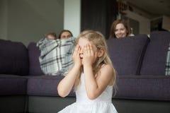 玩与家庭的小女孩闭合值的眼睛捉迷藏 库存图片