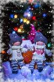 玩偶女孩和一个玩偶男孩雪的在一棵欢乐圣诞树前面 库存照片