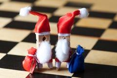玩具圣诞节贺卡概念 两个晒衣夹圣诞老人字符,红色蓝色礼物请求,选择聚焦宏指令 库存图片