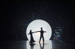 玩具在月亮下的夫妇跳舞剪影在晚上 男人和妇女图爱跳舞的在月光 图库摄影