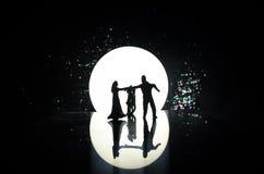 玩具在月亮下的夫妇跳舞剪影在晚上 男人和妇女图爱跳舞的在月光 库存图片