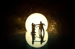 玩具在月亮下的夫妇跳舞剪影在晚上 男人和妇女图爱跳舞的在月光 免版税库存图片
