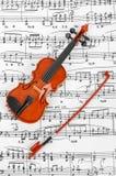 玩具小提琴和音乐纸张 免版税图库摄影