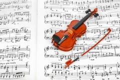 玩具小提琴和音乐纸张 免版税库存照片