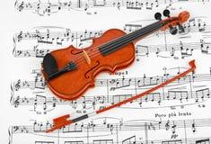 玩具小提琴和音乐纸张 图库摄影