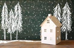 玩具房子照片在黑板前面的有冬天概念图画的 图库摄影