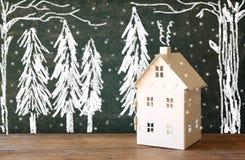 玩具房子照片在黑板前面的有冬天概念图画的 库存图片