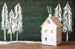 玩具房子照片在黑板前面的有冬天概念图画的 库存照片