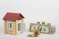 玩具房子近似货币是购买一盒票据和堆硬币 免版税库存图片
