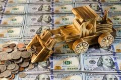 玩具拖拉机倾斜一束美分反对背景  免版税库存照片