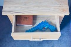 玩具枪和圣经在抽屉 免版税图库摄影