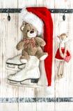 玩具熊、天使和红色圣诞老人帽子有白色的滑冰 免版税库存照片