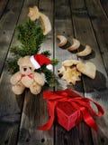 玩具熊、曲奇饼和一项圣诞节礼物在木背景 免版税图库摄影