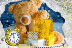 玩具熊、礼物和一个闹钟在圣诞夜 免版税库存图片