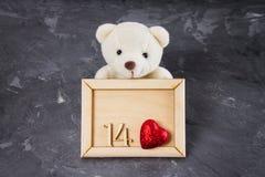 玩具熊和木制框架与图一个和四和心脏在灰色背景 天的标志恋人 华伦泰 库存照片