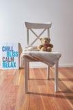 玩具熊和毯子在椅子与海报 免版税图库摄影