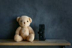 玩具熊和玩具照相机在木地板上和水泥围住backgro 免版税库存照片
