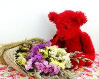 玩具熊和statice开花与打印的织品的花束 库存照片