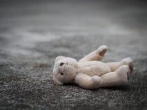 玩具熊在地板上放下 偏僻的概念 Internat 免版税库存照片