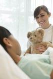 给玩具熊的微笑的女性医生躺下在医院病床上的女孩患者 免版税库存图片