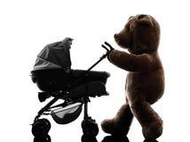 玩具熊走的摇篮车婴孩剪影 免版税库存照片