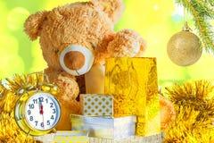 玩具熊,礼物,闹钟,在被弄脏的backgr的圣诞节球 库存图片