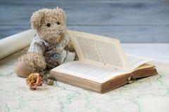 玩具熊读书在老地图的古董书 免版税图库摄影